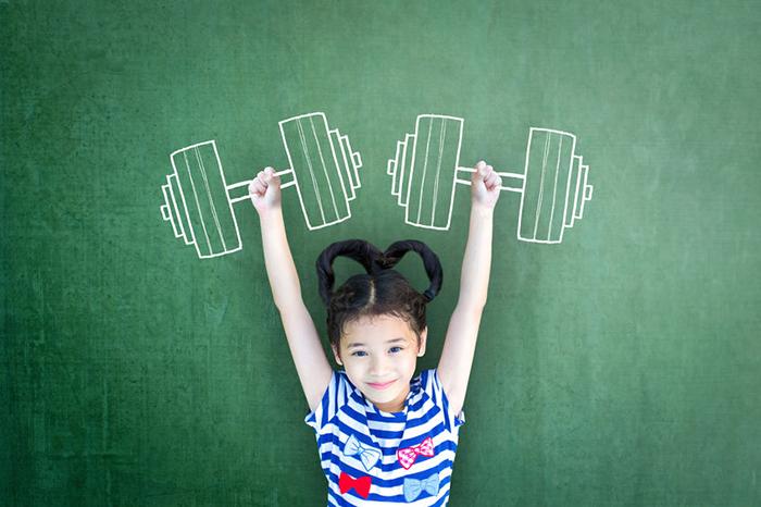 Meisje met gestrekte armen boven haar hoofd voor groen krijtbord waarop haltergewichten zijn getekend
