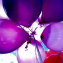 Paarse en rode ballonnen tegen een blauwe lucht om te vieren dat de website live is